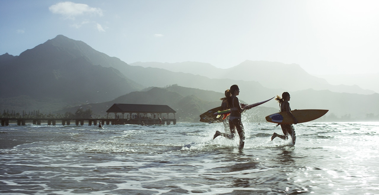 Photo of surfers running out into the water carrying their boards in front of a mountainous landscape