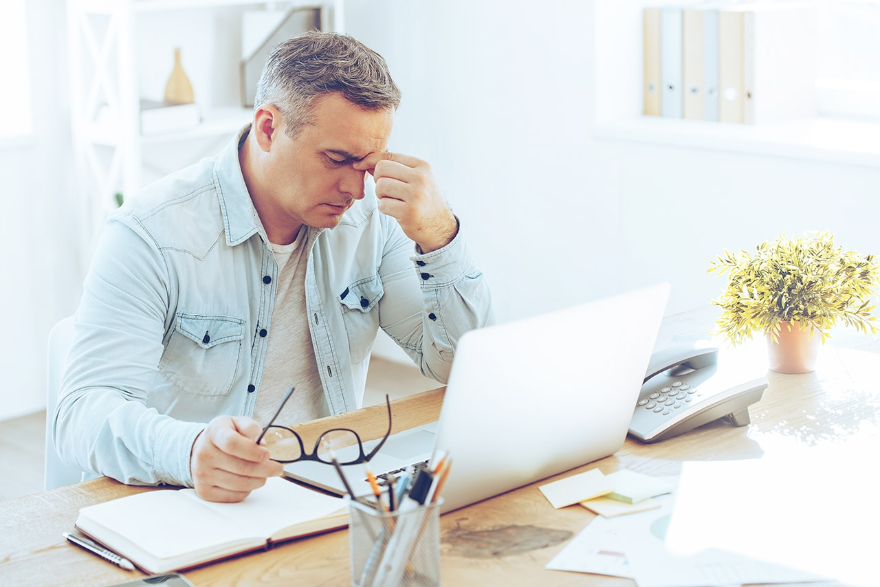 Photo of a person sitting at a desk with their glasses in one hand and the other pinching the bridge of their nose in distress