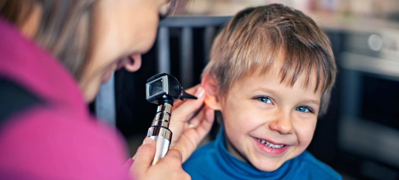 An audiologist holding an otoscope in one hand and a smiling child's ear in the other