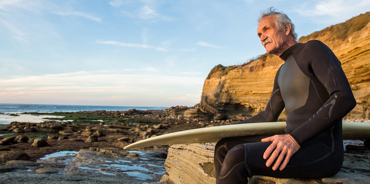 Photo of an older man in a wetsuit holding a surfboard and sitting on rocks near the ocean