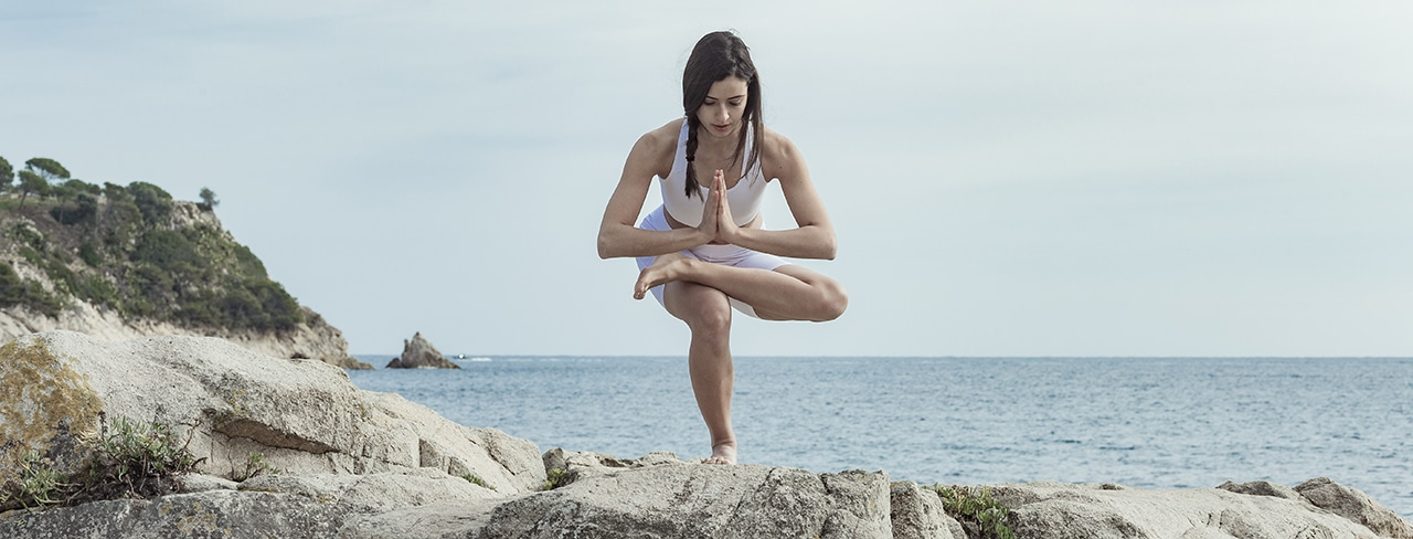 Photo of a woman balancing on one leg in a yoga pose on a rock near the ocean