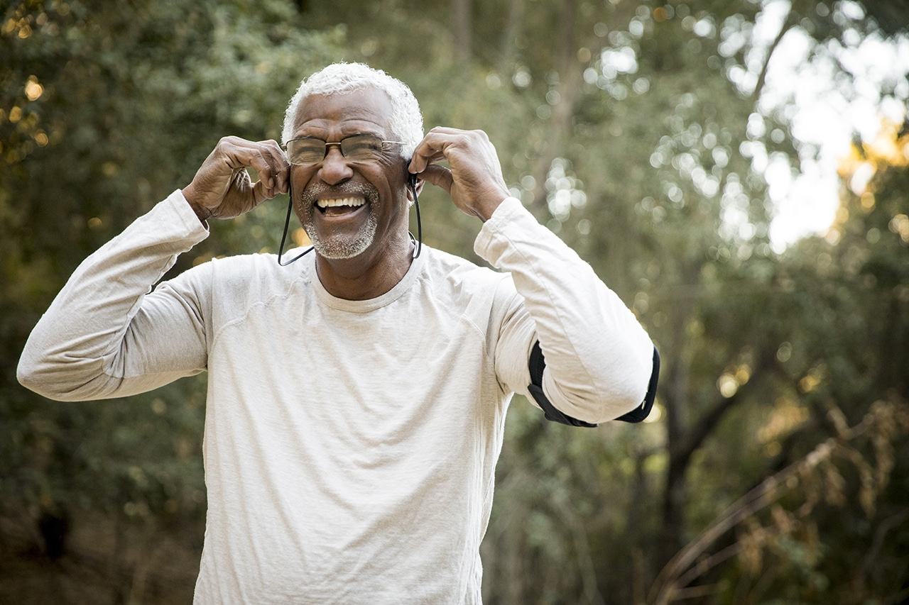 Photo of a person smiling and positioning a set of earbuds