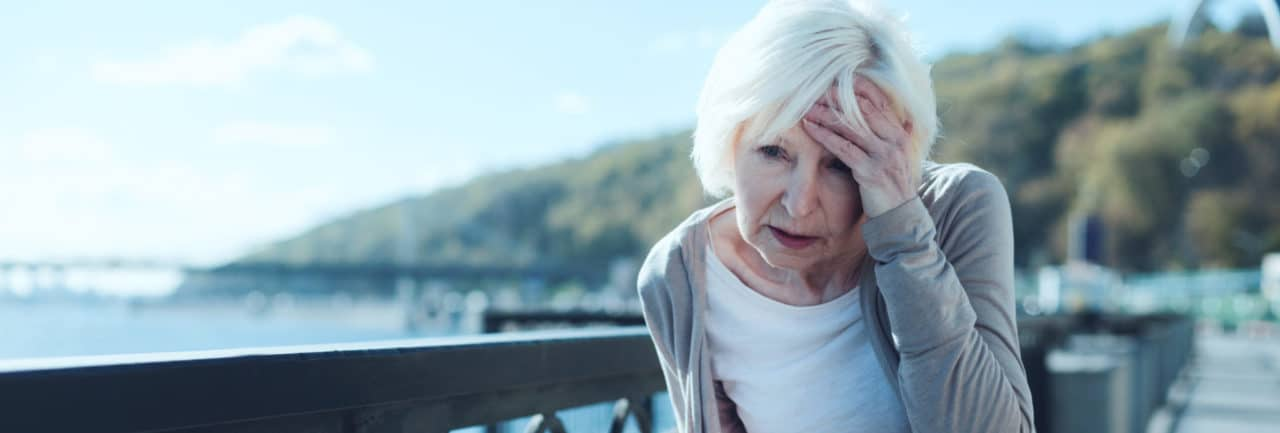 Photo of a person outside on a boardwalk and holding their head in pain, slightly hunched over