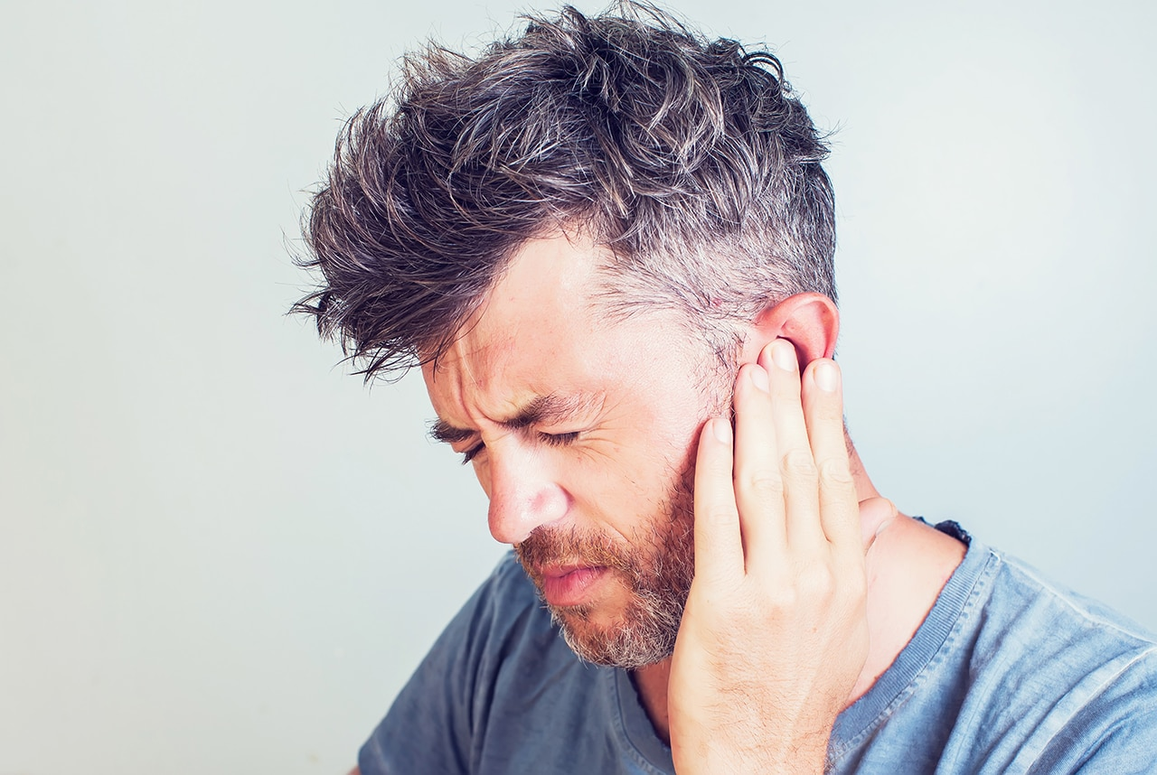 Photo of a person touching their ear and wincing in pain