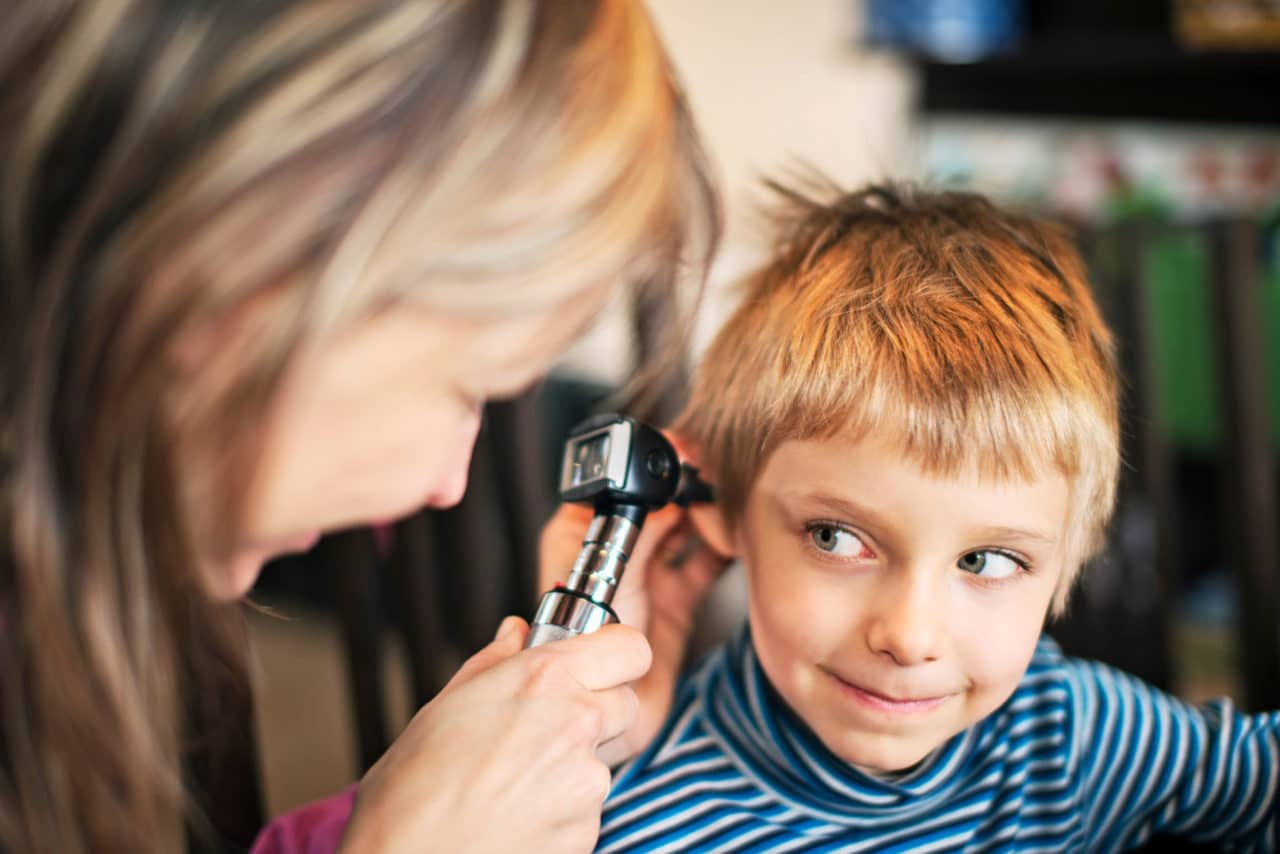 Photo of a child looking up at an audiologist who is examining them with an otoscope