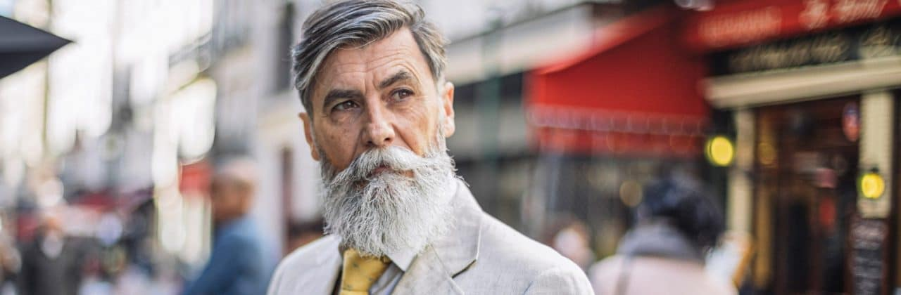 Photo of an older man standing in a city street, looking thoughtful