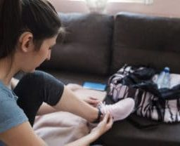 Woman with hearing aid putting on jogging shoes in front of couch