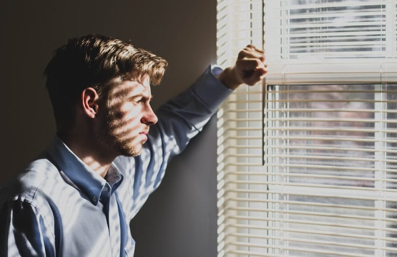 Man looks outside of window