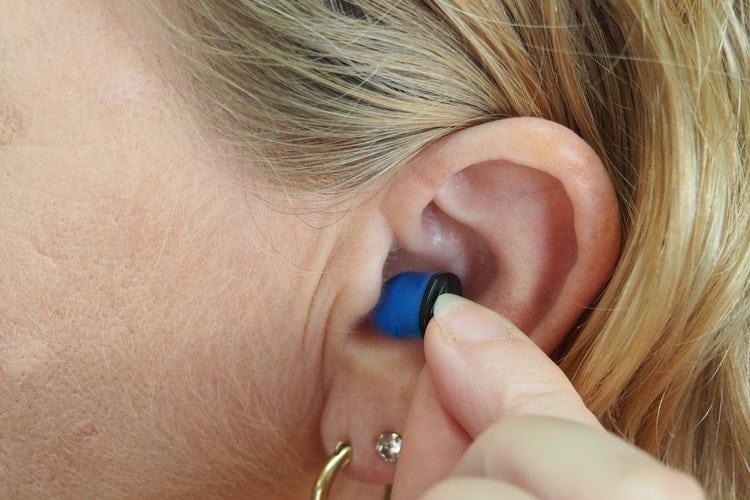 Woman places earplug in her ear