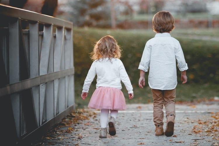 Two children walking on bridge.