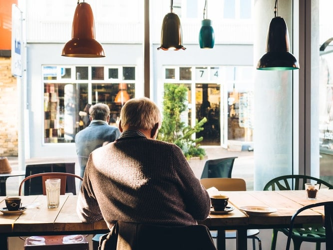 Man sits inside coffee shop.