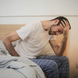 Tired man sitting on edge of bed.