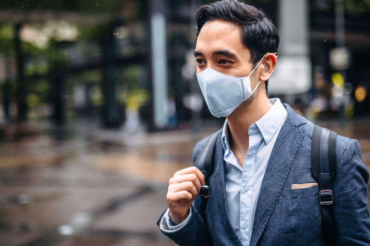 Business man wearing face mask outside.