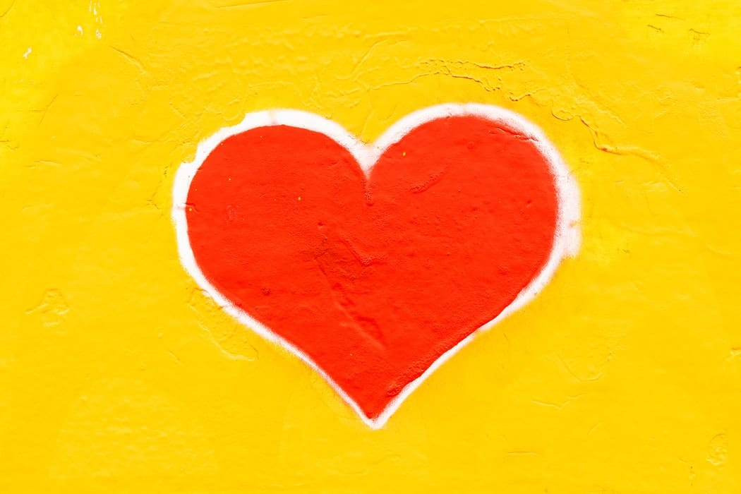 A picture of a red heart with a yellow background.