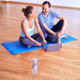 Middle-aged couple sitting together on yoga mat.
