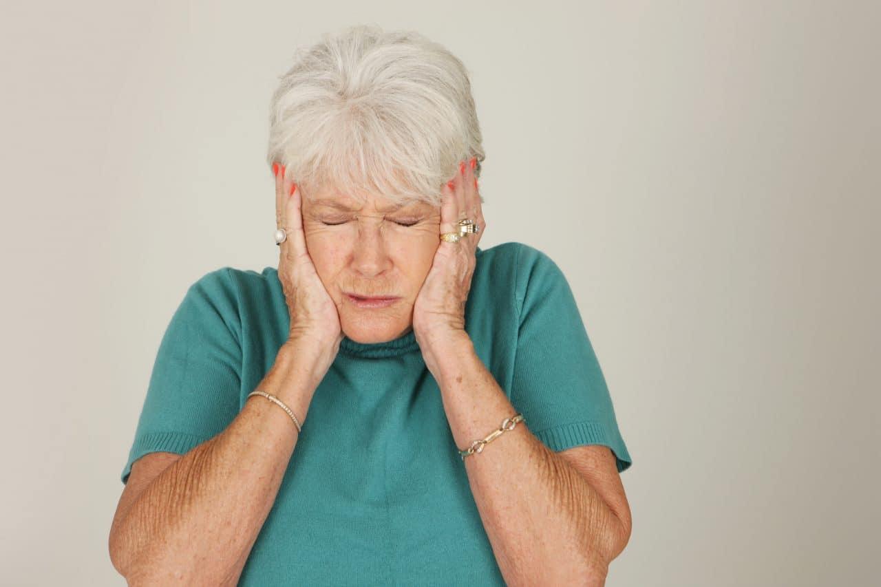 Older woman puts her hands over her ears