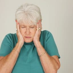 Older woman with hands covering her ears.