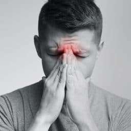 Sad man holding his nose because of sinus pain